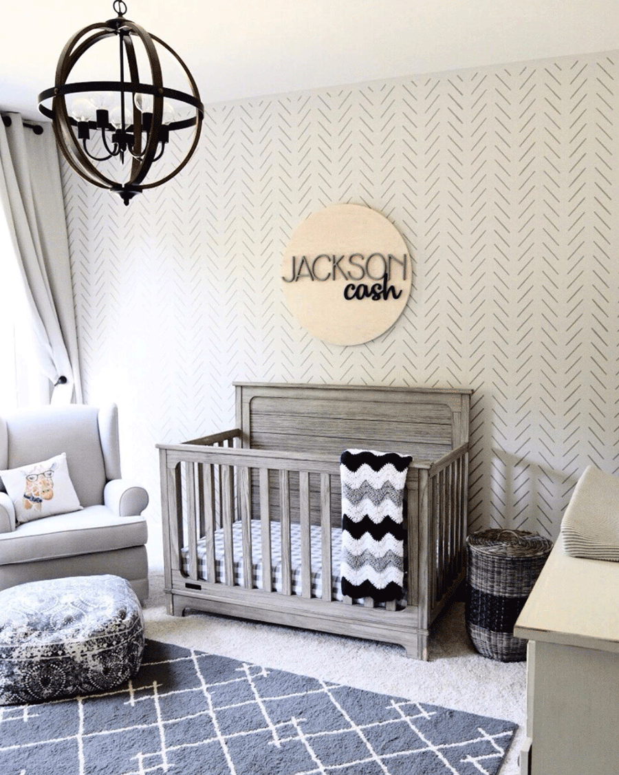 Nursery with stenciled art on the wall.