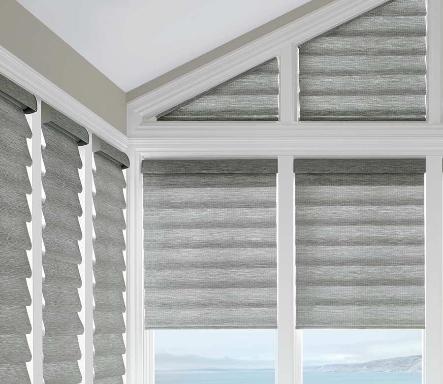 grey roman shades framed by white beams