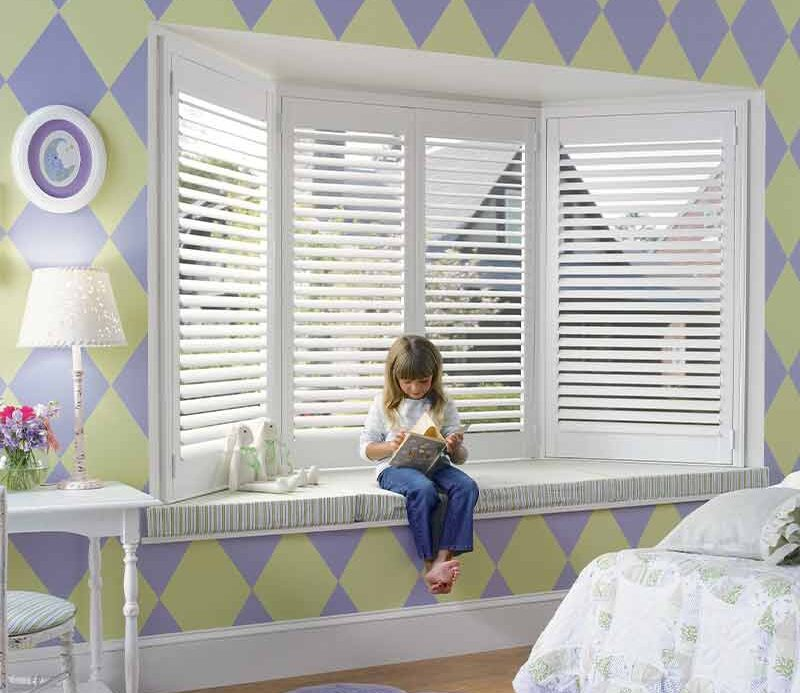 purple and green kids bedroom with white bay window shutters in Naples, FL